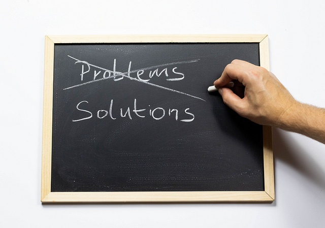 "Person crossing out the word ""Problems"" and replacing it with a word ""Solutions"" in chalk on a blackboard."