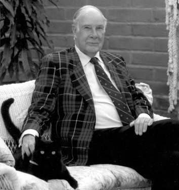 Richard Hamming and a cat seated on a couch, Hamming is wearing a checkered sport coat.