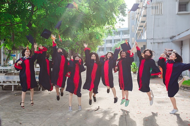 A group of students jumping up for joy having graduated, throwing their caps in the air.