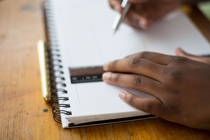 A person using a ruler and pen in a notebook