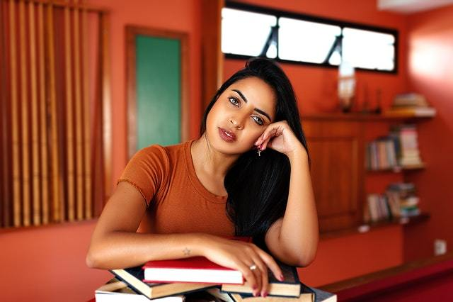 A young woman resting her head on her arm which rests of an a pile of books
