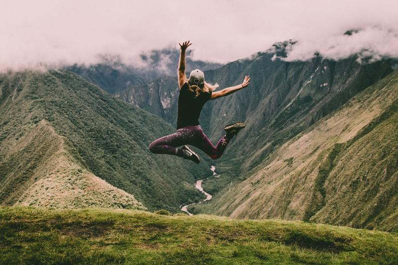 A person jumping up with hands and feet in the air on a mountaintop