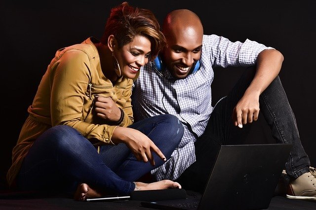 A young couple smiling and watching something on their laptop screen, the woman is pointing something out to the man.
